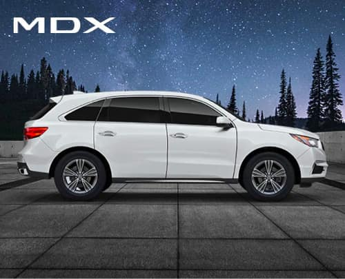 Side view of white Acura MDX in front of night sky