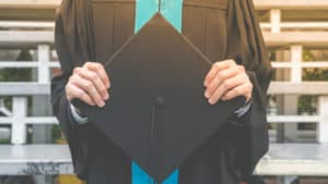 College grad in black cap and gown with teal stole