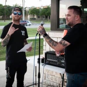 Cowboy Harley Davidson Party With Us Pic One man with microphone and another man with paper in his hand