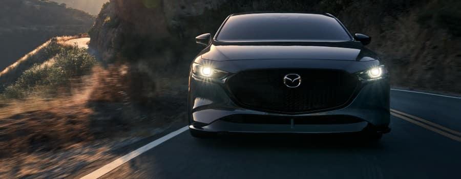 A 2021 Mazda3 driving with its headlights on - El Dorado Mazda in McKinney, Texas