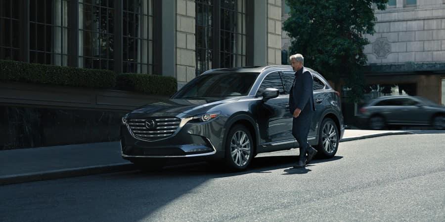 A man standing next to a 2021 Mazda CX-9 - El Dorado Mazda in McKinney, Texas