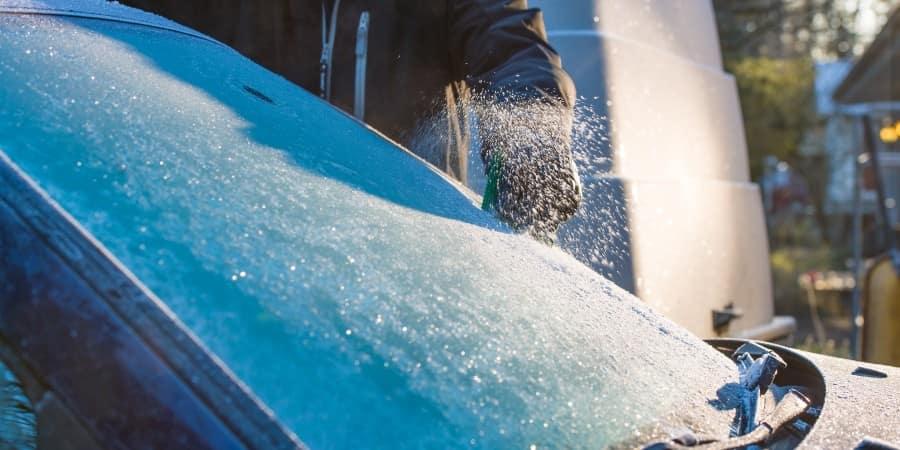 A person scraping a frozen windshield - El Dorado Mazda in McKinney, Texas