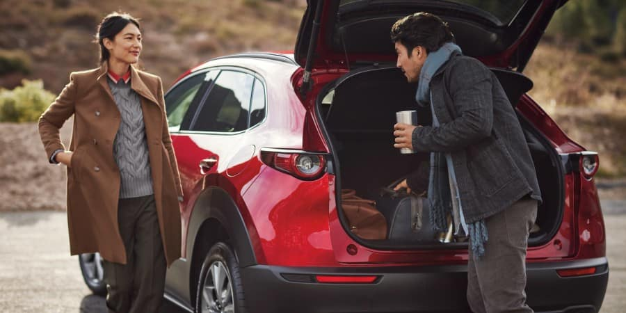 A man and woman packing items into a red 2020 Mazda CX-30 - El Dorado Mazda in McKinney, Texas