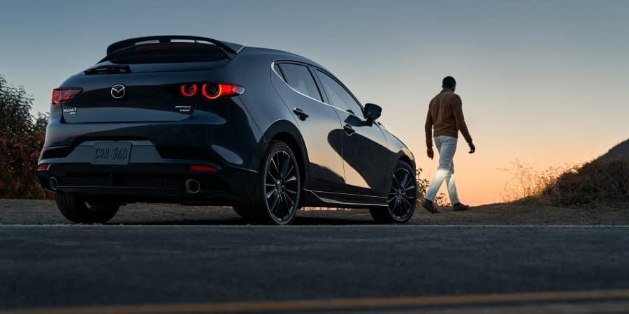 A man standing next to a 2021 Mazda3 Hatchback - El Dorado Mazda in McKinney, Texas