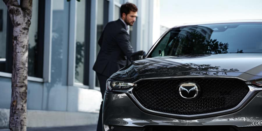 A man standing next to a gray 2020 Mazda CX-5 - El Dorado Mazda in McKinney, Texas
