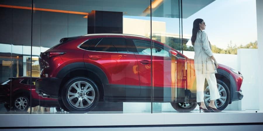 A woman standing next to a red 2020 Mazda CX-30 - El Dorado Mazda in McKinney, Texas