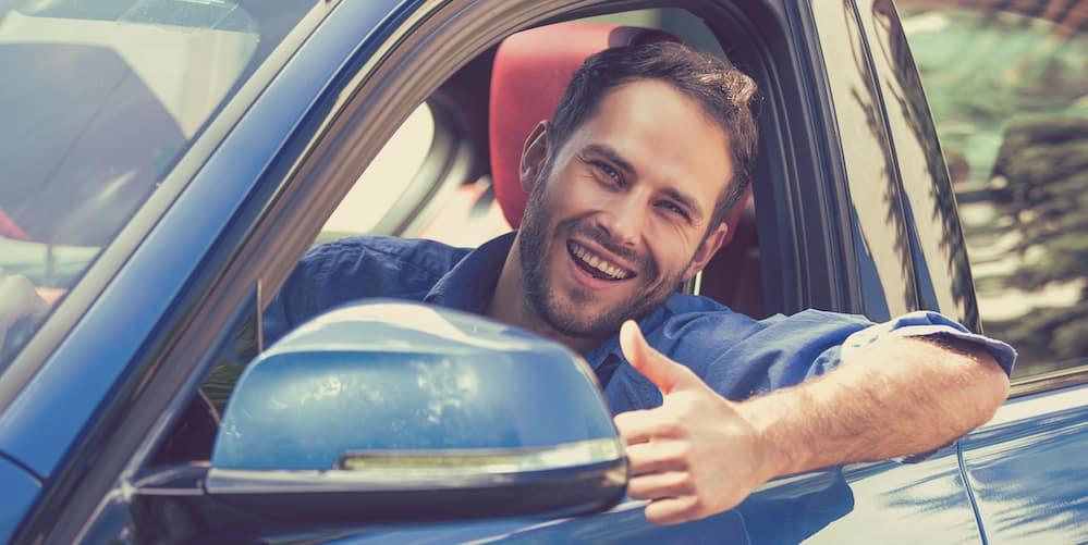 Man Giving a Thumbs Up from a Used Car