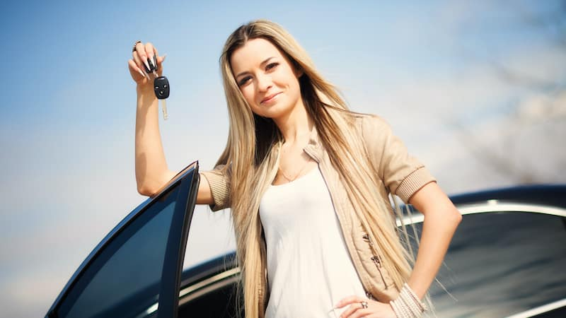 Woman Holding Key to Car