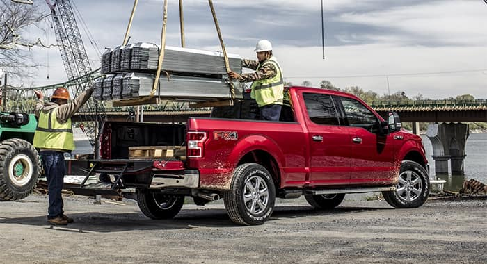 Construction workers loading product into Ford F-150 Bed