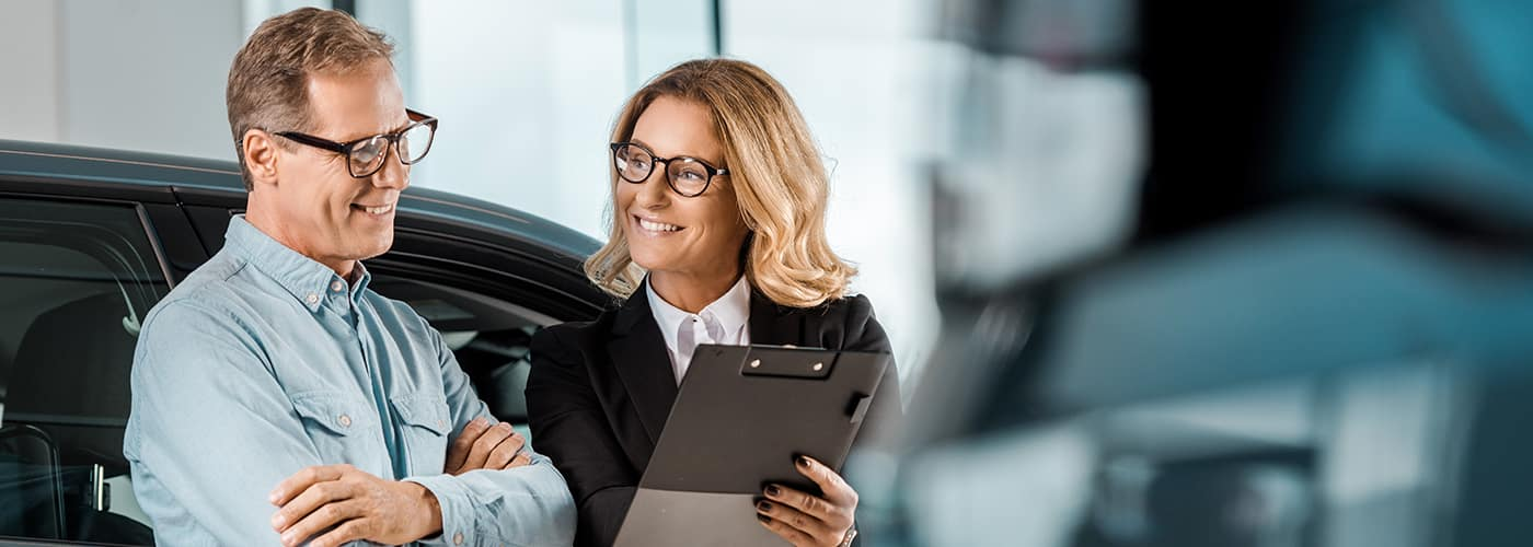 Sales Woman Going Over Leasing Document with Customer