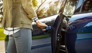 person opening the driver door of a blue Toyota vehicle