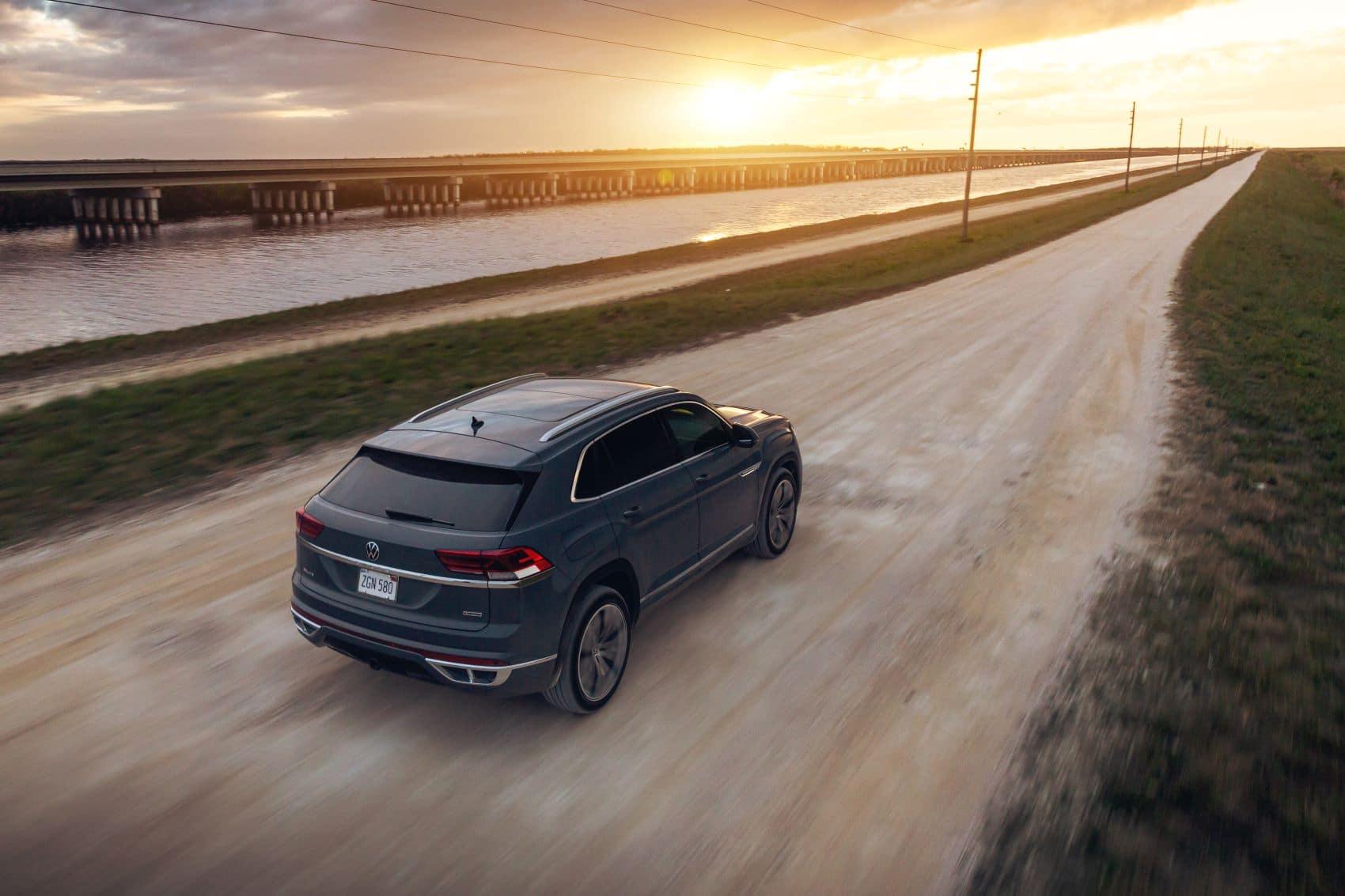 Tourmaline Blue Metallic VW Atlas Cross Sport driving on a dirt road