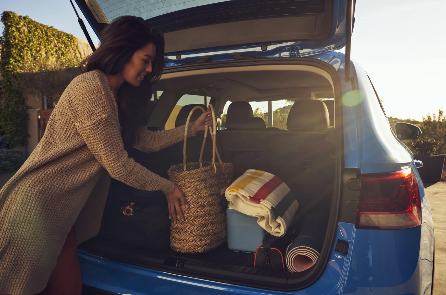 2022 Volkswagen Taos blue cargo area rear hatch up woman packing bags
