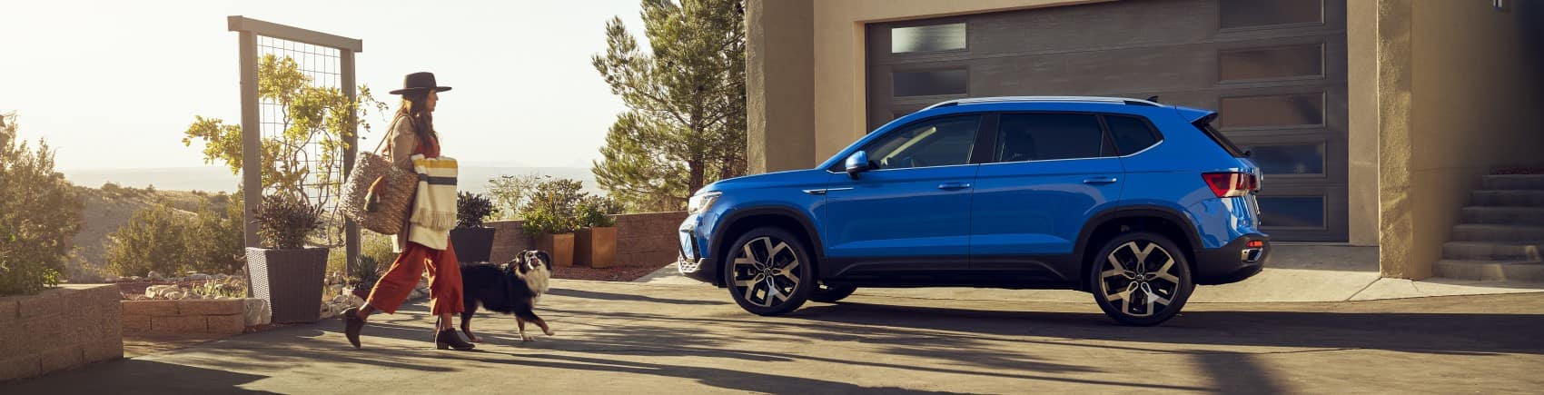 2022 Volkswagen Taos blue profile shot parked in driveway banner