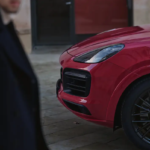 A person walking past a red 2021 Porsche Cayenne