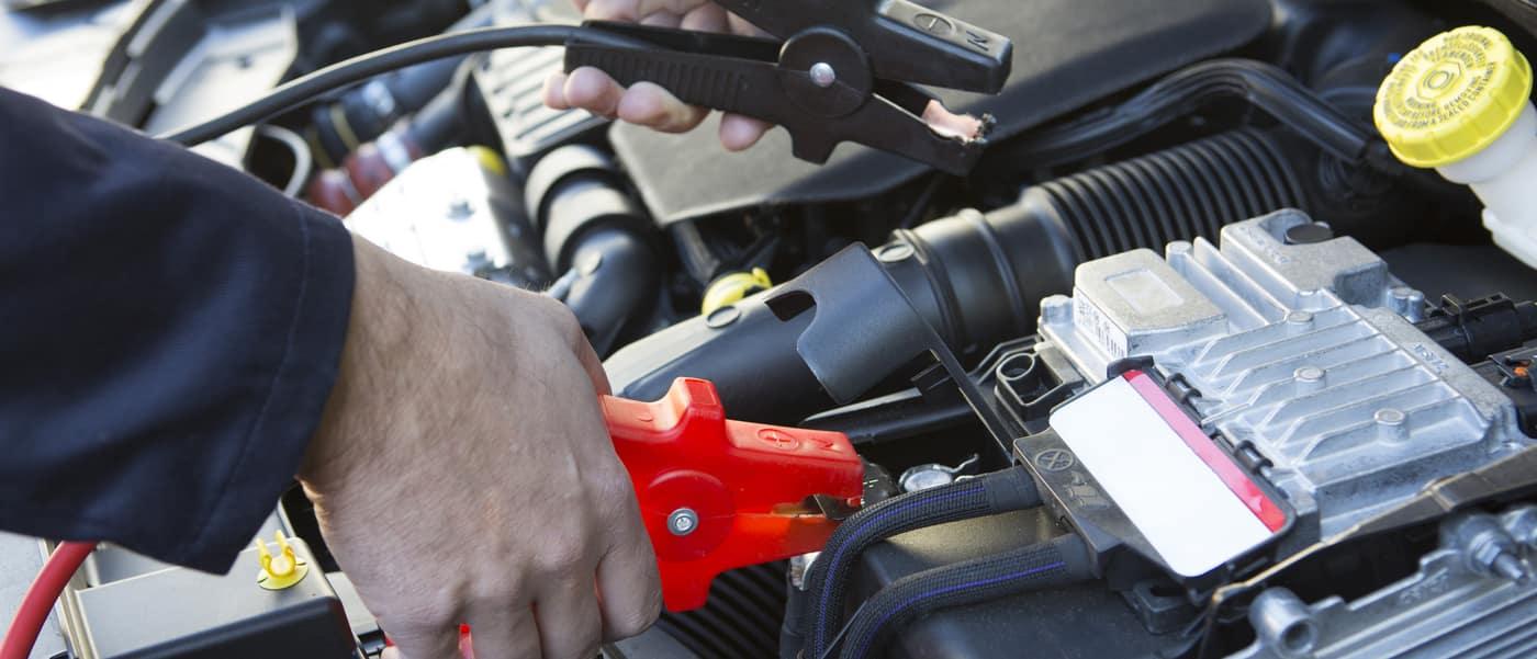 mechanic jump starting a car