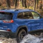 blue jeep cherokee driving through water