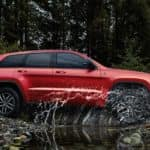 red jeep grand cherokee driving through large puddle