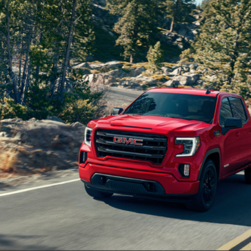 Picture of a red 2020 GMC Sierra driving up a hill