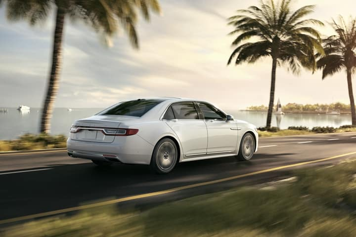 A white 2020 Lincoln Continental drives by the beach.