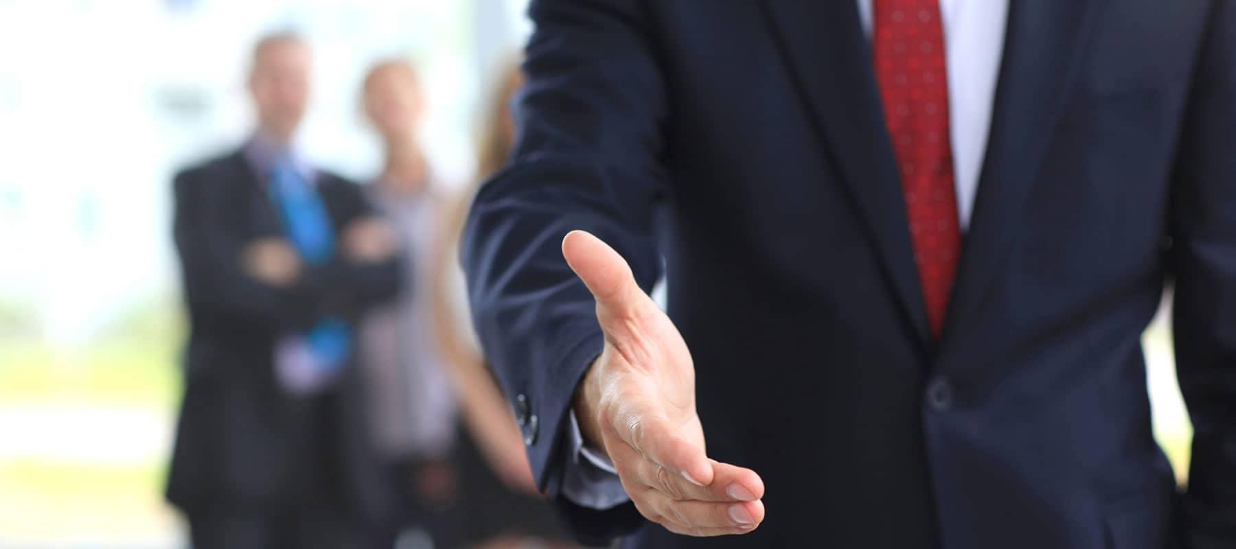Person in suit extending hand for handshake